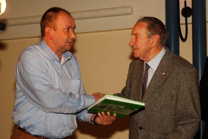 Charley van de Weerd (rechts) ontvangt in 2007 het eerste exemplaar van Het Groenwitte Bolwerk, de geschiedenis van het voetbal op de Wageningse Berg van 1911 tot 1954, uit handen van Rien Bor. Zoon Chris van de Weerd overleed deze week.