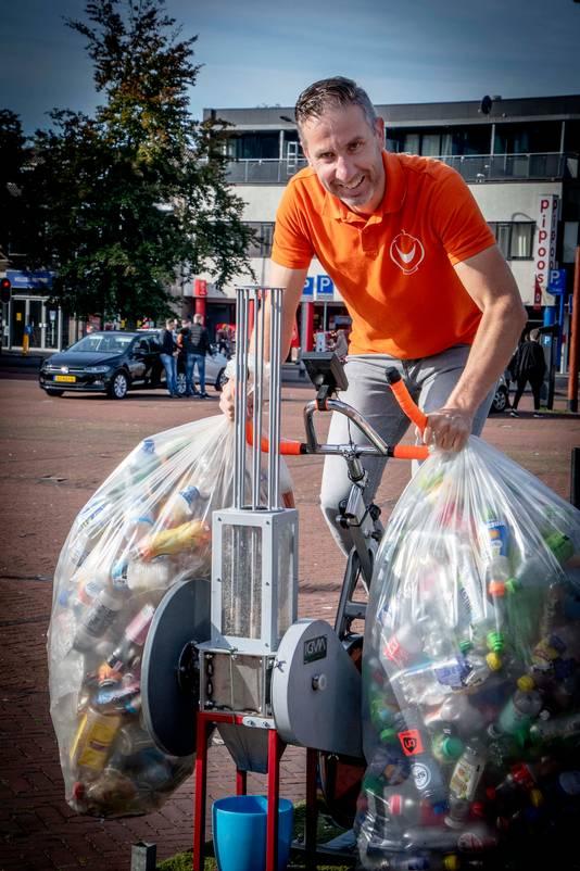Rolph Adriaansen op de speciale fiets. Hij wil van duizenden vermalen flesjes ook nog een kroonluchter maken voor de LocHal.