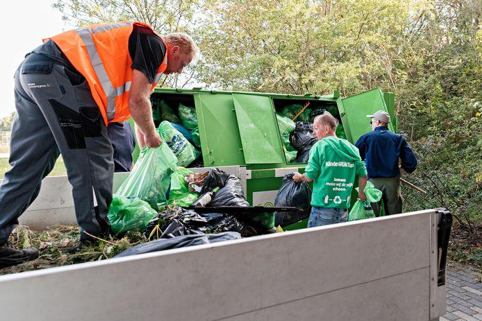 Deelnemers aan World Clean Up Day laden het zwerfafval over van een vrachtwagen in een container.