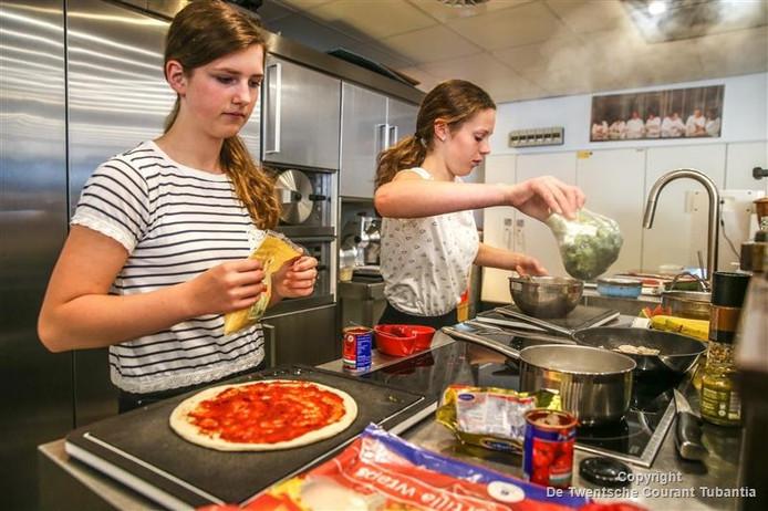 Twee leerlingen van scholengemeenschap Het Noordik Vriezenveen - Joyce Jansen Smit en Merle Companjen - bezig met bakken gezonde pizza in finale IRun2BFit menu in kookstudio drie sterren restaurant De Librije.