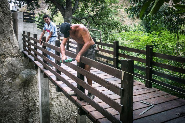 Een migrant bouwt aan een brug in Riace. Beeld Nicola Zolin