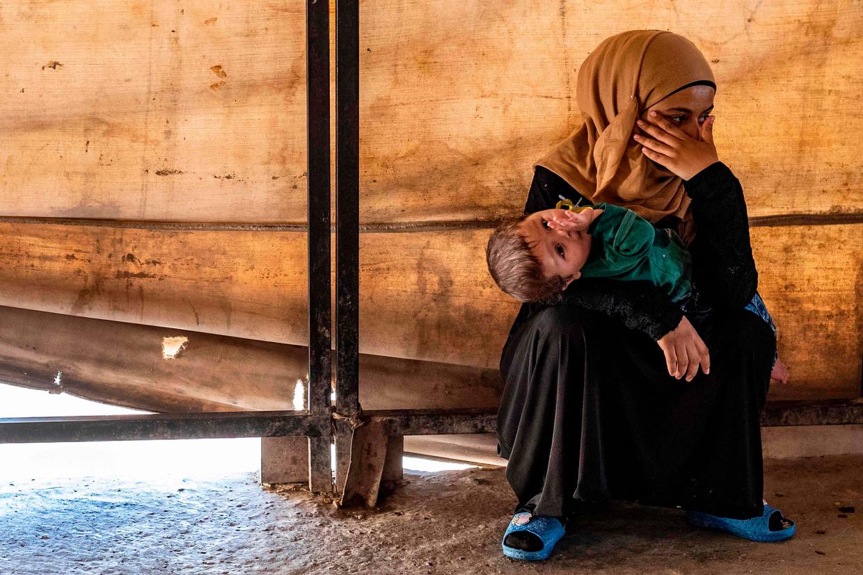Een vrijwilliger die zorg draagt voor een van de 24 weeskinderen, die vermoedelijk familie zijn van IS-strijders, in Ain Issa.