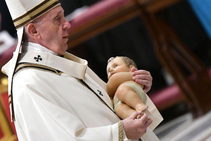 Paus Franciscus met in zijn handen een beeld van kindje Jezus.
