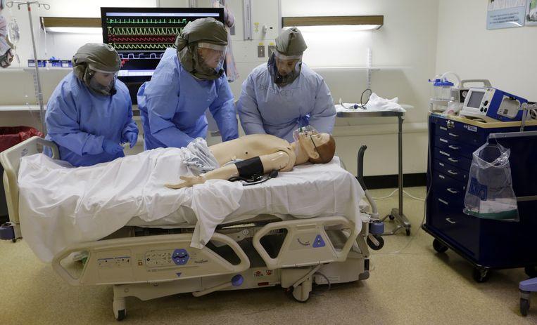 Verpleegkundigen oefenen in beschermende kleding op een pop. Beeld ap