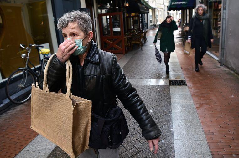 Een bezorgde vrouw in een winkelstraat in Den Bosch, woensdag 11 maart 2020. Veiligheidsregio's in Brabant kondigden de avond ervoor een sociale onthouding van een week aan, premier Rutte riep op te stoppen met handen schudden. Beeld Marcel van den Bergh