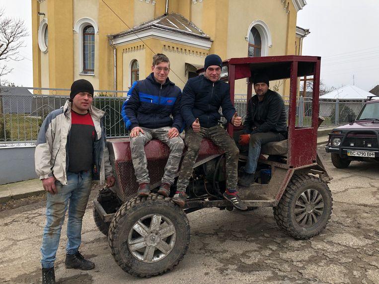 'Traktorist' Volodja Volosjin achter het stuur van zijn zelfgebouwde trekker, in gezelschap van enkele dorpsgenoten. Beeld Michiel Driebergen