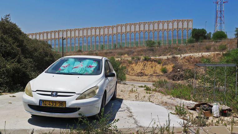 De muur in Netiv HaAsara tegen scherpschutters, met daarachter het hek om de Gazastrook. Beeld Geert van Kesteren