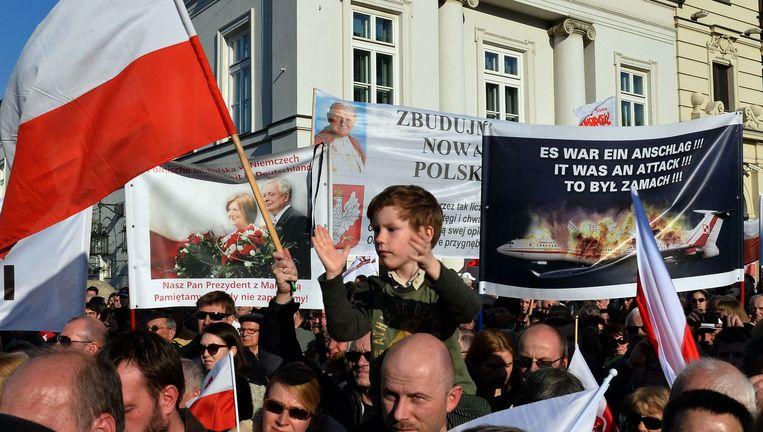 De aanhangers van de partij van Kaczynski houden hun eigen herdenking en dragen spandoeken mee waarop de vliegramp een aanslag wordt genoemd, met een rol voor de Russische president Poetin. Beeld AFP