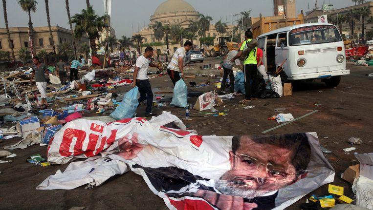 Egyptenaren verzamelen nog bruikbare spullen bij het platgewalsde tentenkamp op het Nahdaplein in Caïro. Beeld ap