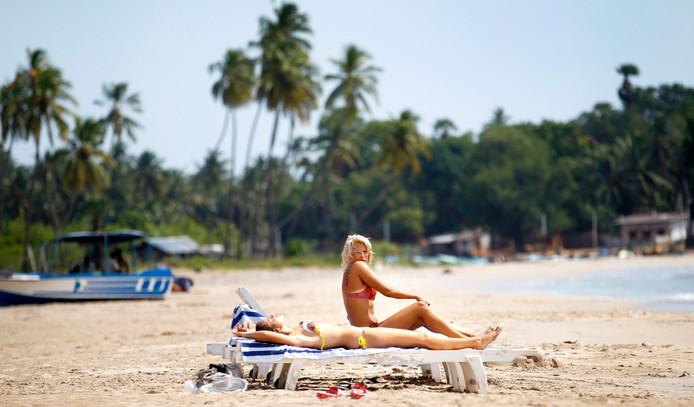 Toeristen zonnebaden aan het strand van Trincomalee, Sri Lanka