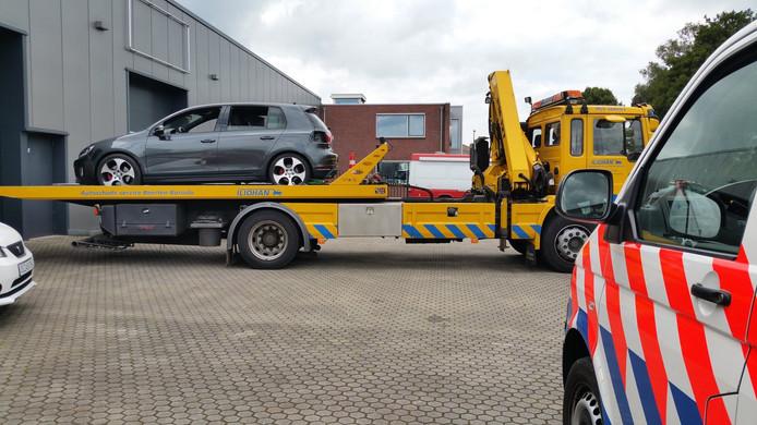 De deels gestripte Volkswagen wordt de loods uit gereden.