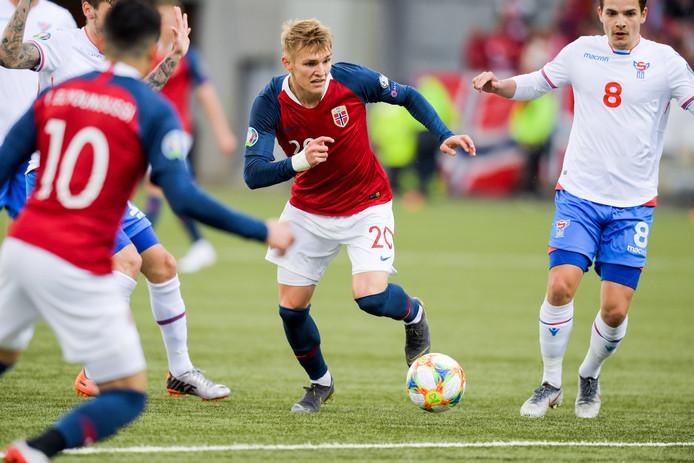 Martin Ødegaard (midden) voor Noorwegen in duel met Brandur Hendriksson van de Faeroër Eilanden.