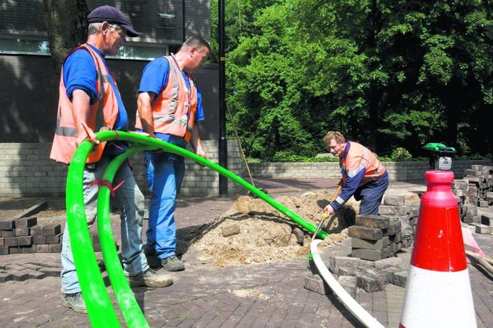 De kabels voor het glasvezelnetwerk gaan de grond in, zoals hier in Zevenaar. foto Henk Rodrigo