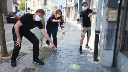 Handelaars en winkelstraten klaar voor heropening maandag, stickers wijzen in Ninoofs dialect op eenrichtingsverkeer op voetpaden