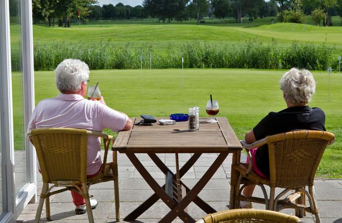 Ouderen genieten van een drankje op een terras bij de golfbaan in Amsterdam.