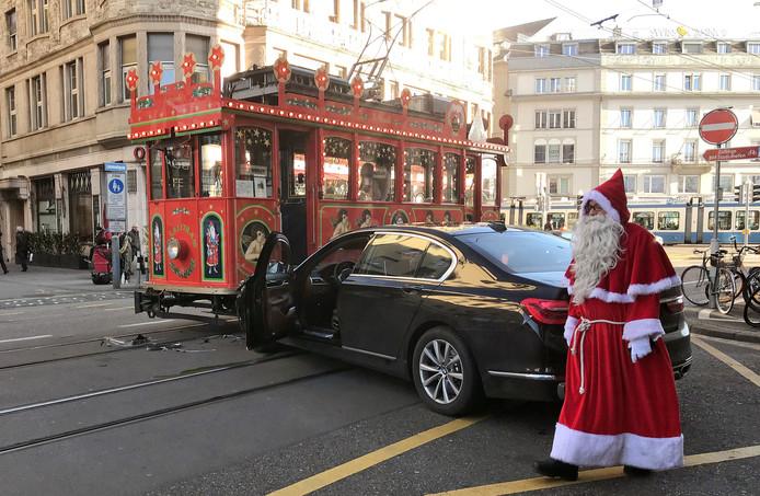 De tram bestuurder verkleed als de kerstman loopt wat beteuterd langs de auto die zojuist zijn tram heeft geramd in Zurich. Foto Angelika Gruber