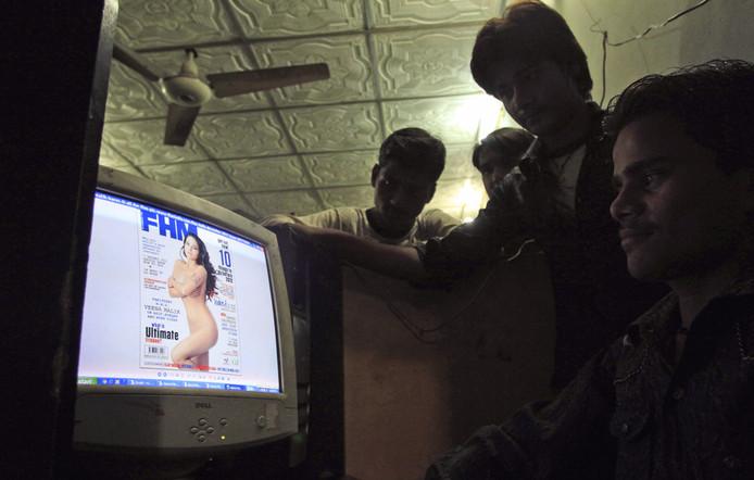 Pakistanen bekijken in een internetcafé de cover van FHM India met de naaktfoto van Veena Malik.