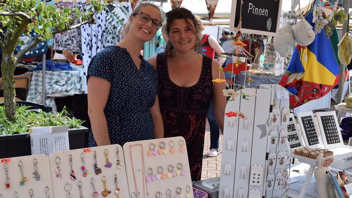 Claudia Willemsen en Leandra Siersma achter hun kraam vol handgemaakte kinderartikelen. ,,We delen vaker samen een markt.''