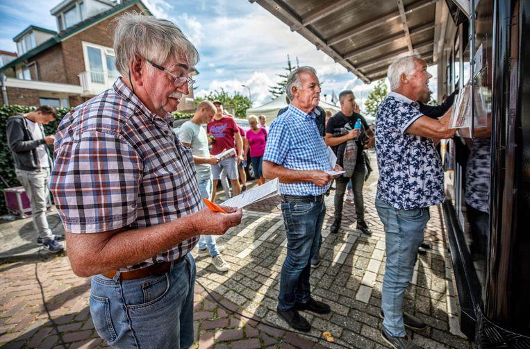 Inwoners van Hillegom wagen een gokje bij  het mobiele wedkantoor van Runnerz. Beeld Raymond Rutting / de Volkskrant