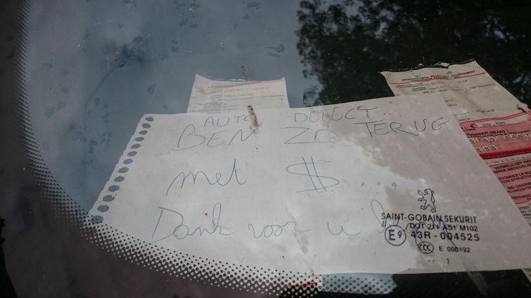Bij de boetes ligt een briefje met de boodschap: 'Auto defect, ben zo terug met $. Dank voor uw begrip'.