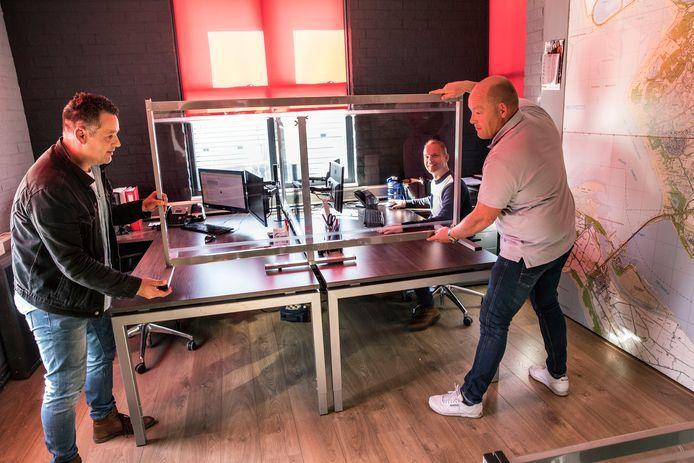 Ondernemers Johan Tjallinks (l) en Rick de Koning plaatsen het scheidingsscherm op het bureau van hun kompaan Arco Regtvoort, van de Alphense tentenbouwer Kontent Structures.