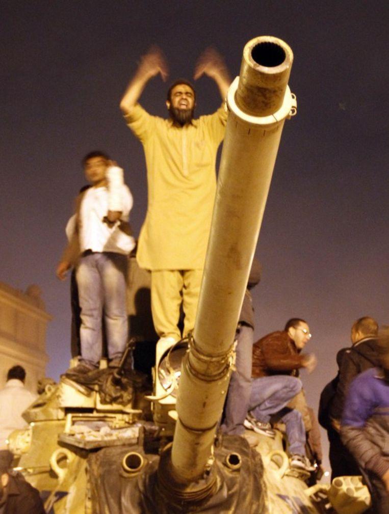 Een Egyptische anti-overheidsdemonstrant schreeuwt 'Allah is groot' terwijl hij op een legertank staat op het Tahrir-plein in Caïro. Beeld afp