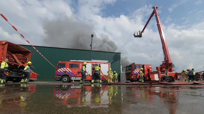 De brandweer bestrijdt het vuur in de hoop schroot.