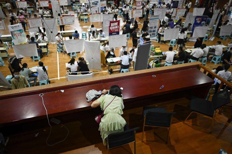 In China worden banenmarkten drukbezocht, nu er door het coronavirus veel werkloosheid is.  Beeld AFP