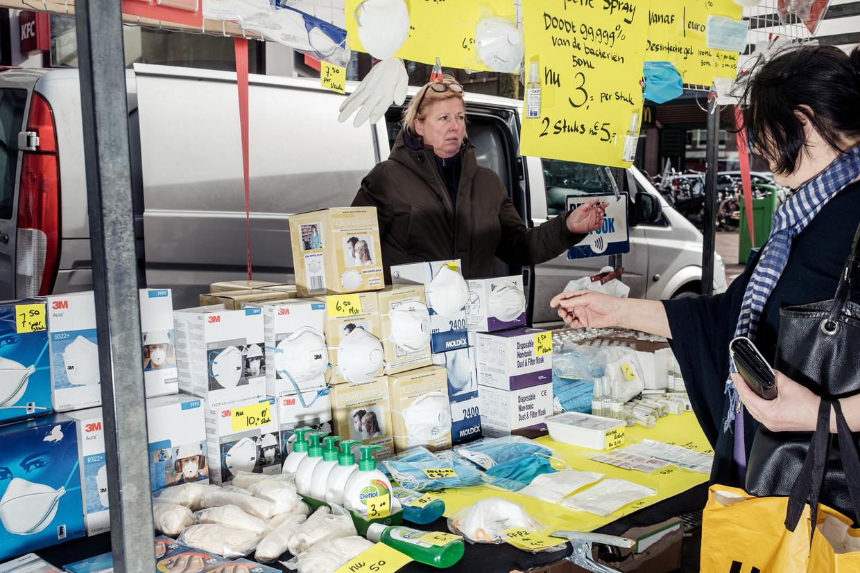 'Coronastalletje' op de Dappermarkt met desinfecteermiddelen en mondkapjes: gaan we die trouw dragen? Beeld Jakob van Vliet