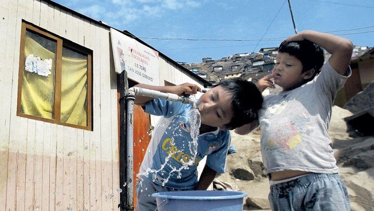 Jongetjes drinken uit een openbare kraan in de sloppenwijk Nueva Esperanza in Lima. Beeld AP