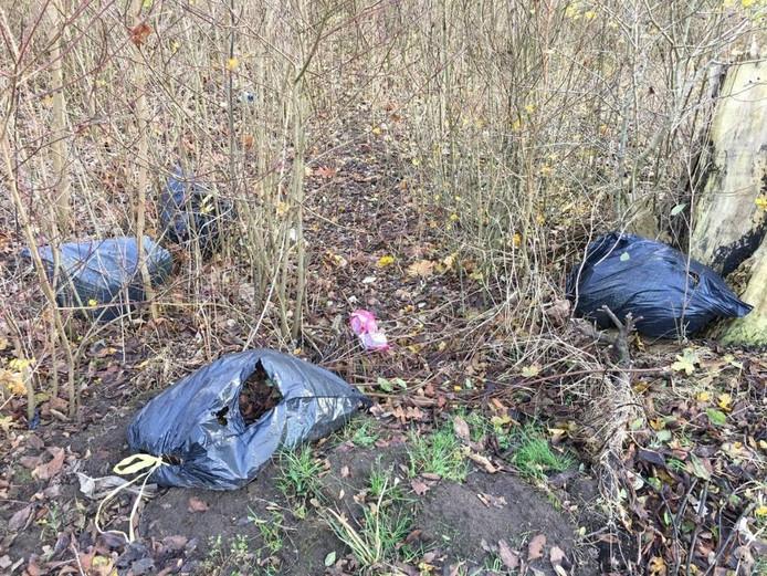 De in de natuur gedumpte afvalzakken.
