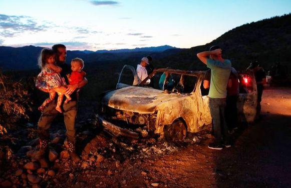 Familieleden treuren bij de uitgebrande wagen na de moordpartij.