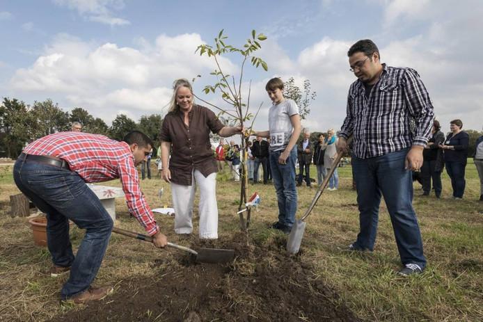 Gedeputeerde Hester Maij plant samen met enkele Syrische statushouders een boom in de Generatietuin.