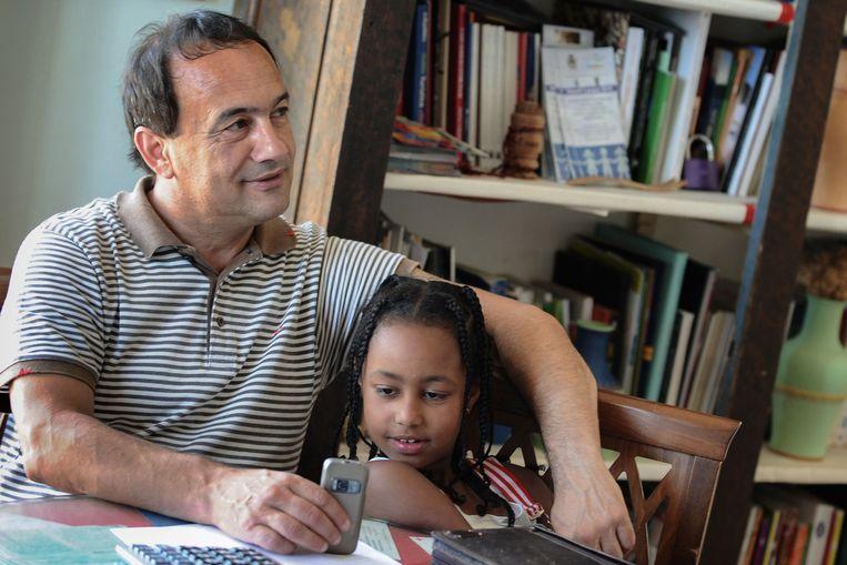 Foto uit 2011 van burgemeester van Riace Domenico Lucano met een jong meisje uit Ethiopië
