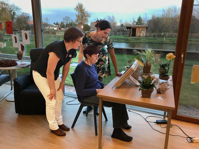 Patricia (zittend) aan het werk op de Brain Trainer, samen met haar dochter Chris (achteraan) en projectverantwoordelijke Annelies (links) in het KYMA-huis in Dessel.