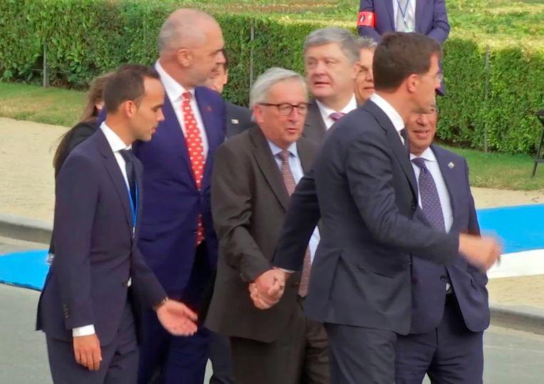 Juncker werd gisteren strompelend gespot bij de groepsfoto op de NAVO-top. Hij moest onder andere door Nederlands premier Mark Rutte ondersteund worden.