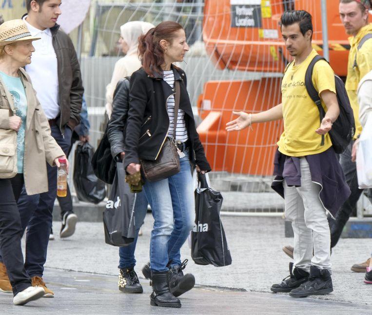 Een medewerker probeert op straat mensen aan te spreken.