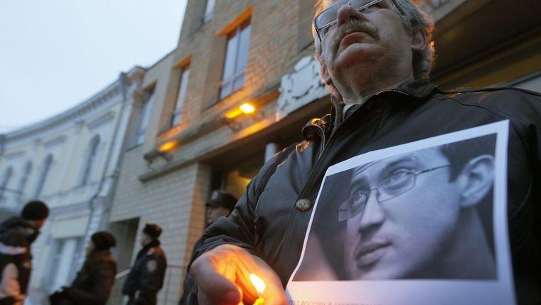Een vriend van Dolmatov toont zijn portret tijdens een demonstratie voor de Nederlandse ambassade in Kiev. Beeld epa