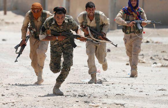 Koerdische YPG-strijders in juli vorig jaar in de straten van Raqqa.