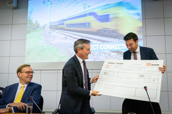 Thomas Geisel (m) geeft een symbolisch treinkaartje aan wethouder Robert van Asten.