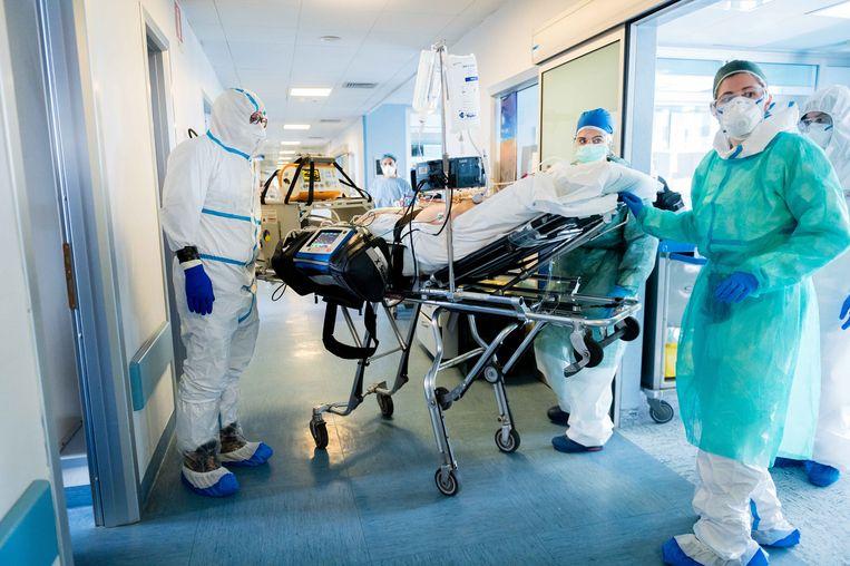 Italiaanse artsen vervoeren een patiënt.  Om de Italiaanse ziekenhuizen te ontzien neemt Duitsland patiënten over.  Beeld Getty Images