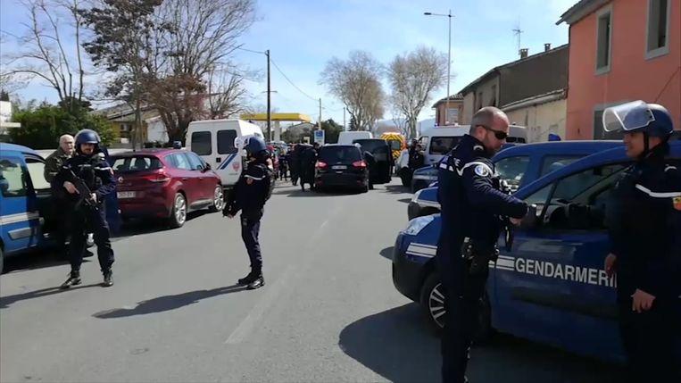 De politie is met een groot aantal manschappen aanwezig aan de supermarkt.