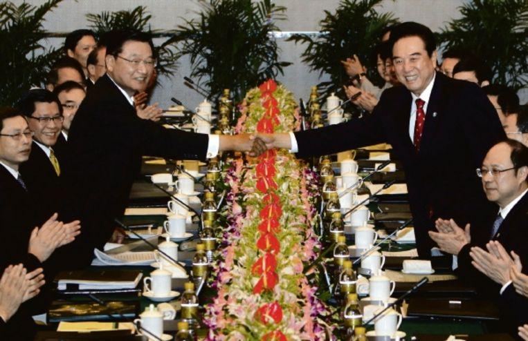 De voorzitters van de onderhandelingsdelegaties van Taiwan (links) en China schudden elkaar de hand. (FOTO REUTERS) Beeld REUTERS