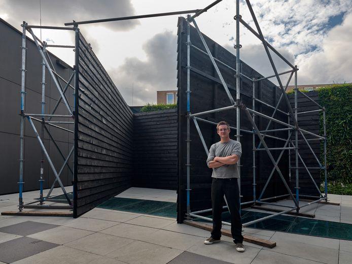 Peter Bouwmans in de binnentuin van het Stedelijk Museum in Breda bij de gepotdekselde muren die hij daar optrok.