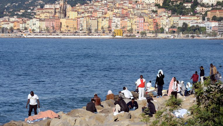 Tientallen vluchtelingen hebben afgelopen weekend de nacht doorgebracht op de rotsen van Ventimiglia, Italië. In de achtergrond is de Franse stad Menton te zien.
