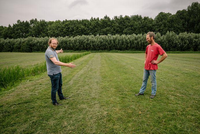 Houtenaar Ruben Berendts (l.) legt bij 't Goy aan veehouder Arjen Vernooij uit waar de windturbine op diens land komt te staan.