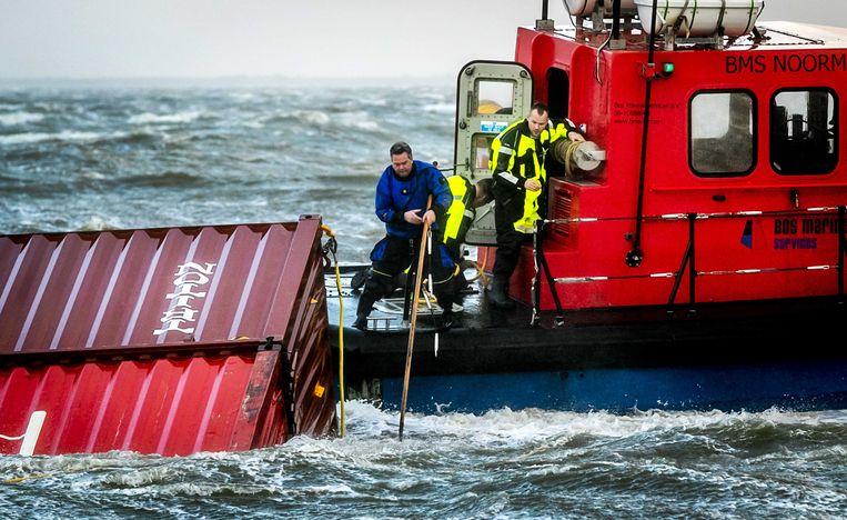 Bemanning van een sleepboot trekt een omgeslagen container van de MSC Zoe aan boord, kort na de ramp. Beeld EPA