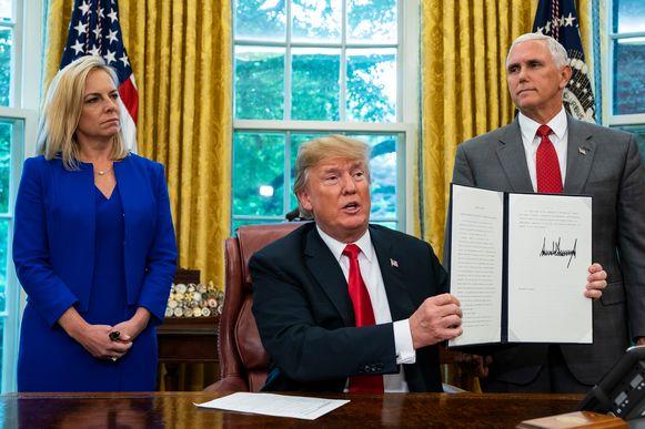 Trump ondertekende vanavond het besluit, geflankeerd door minister van Binnenlandse Veiligheid Kirstjen Nielsen (l.) en vicepresident Mike Pence.