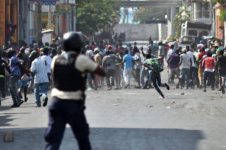 Demonstranten vluchten weg terwijl de Haïtiaanse politie het vuur opent.