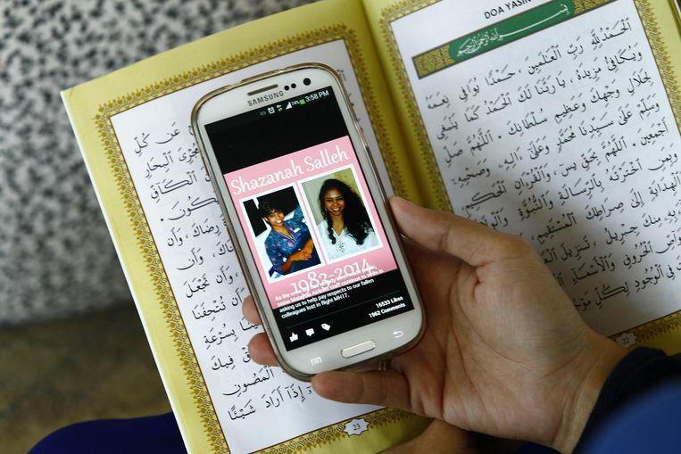 Nur Shazana Mohamed Salleh op een foto op een mobiele telefoon van een oud-klasgenoot, tijdens een gebedsbijeenkomst voor de slachtoffers van vlucht MH17. Beeld reuters